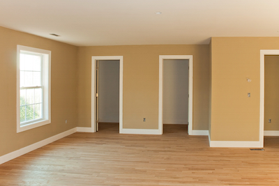 New home construction interior room with unfinished wood floors and twin closets.